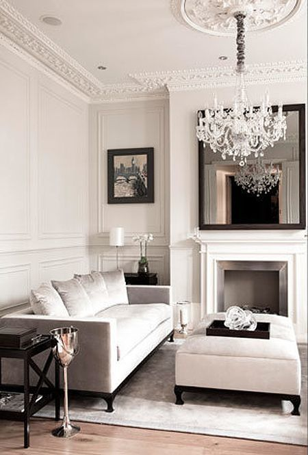 molding on the walls and ceiling and a glam crystal chandelier define this living room
