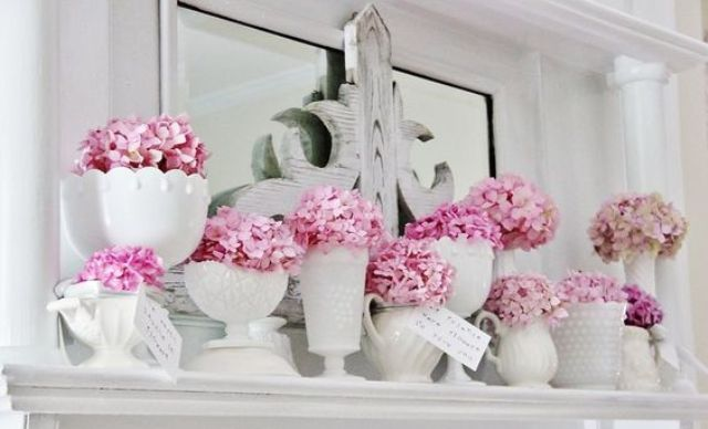 pink blooms in vases and jars of different look for a shabby chic spring mantel
