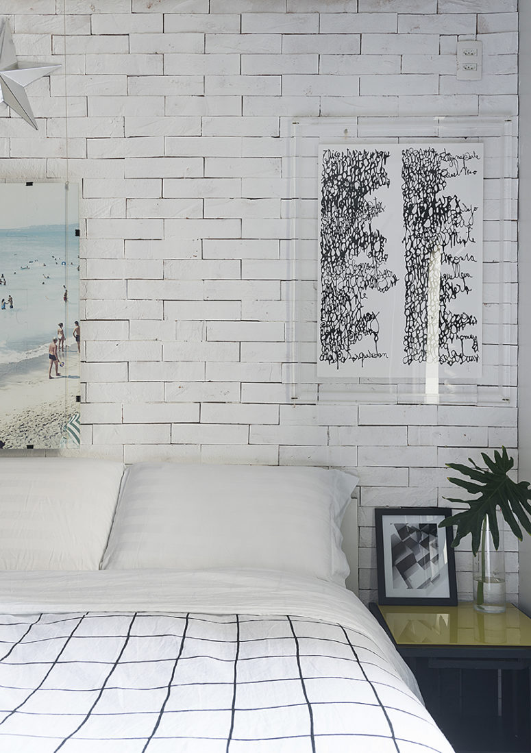 On of the two bedrooms with a faux brick wall, bold artworks is filled with natural light