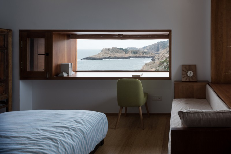 One of the bedrooms with a large windowsill desk, a comfy sofa and amazing views