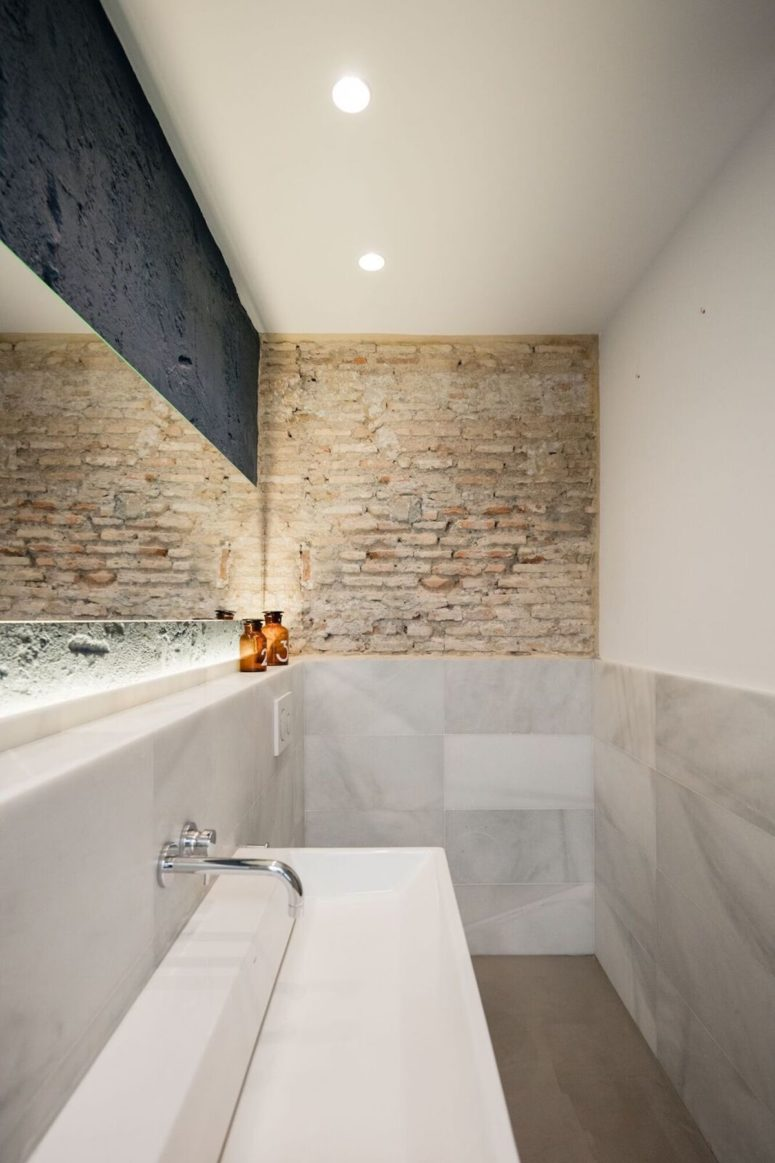 The bathroom also features exposed brick like everywhere else, built-in lights and marble