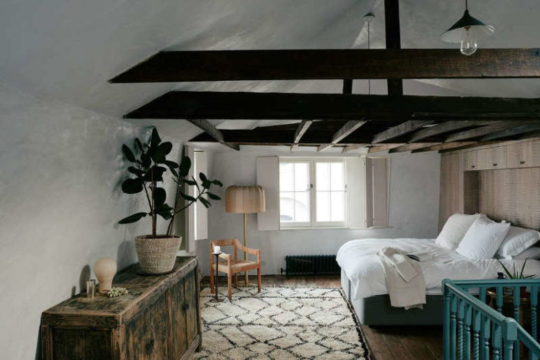 The bedroom is done with dark wooden beams, an antique sideboard and rather contemporary furniture and rugs