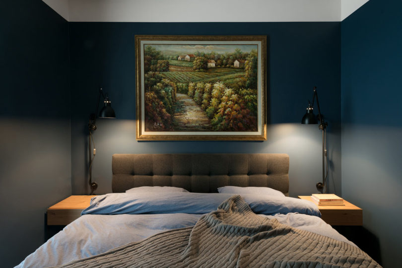 There's an upholstered bed, some lamps and an artwork