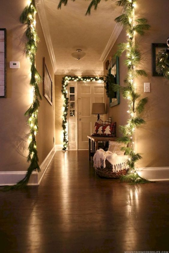 cover the door and archways with string lights to make it shine, here they are combined with faux fir garlands for the holidays