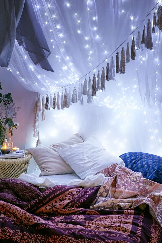 string lights attached to the bed canopy create a galaxy-like effect and look wow