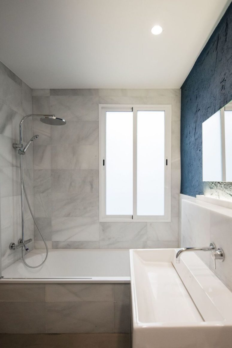 Marble is seen in the other part of the bathroom, too, and there's much light in the space