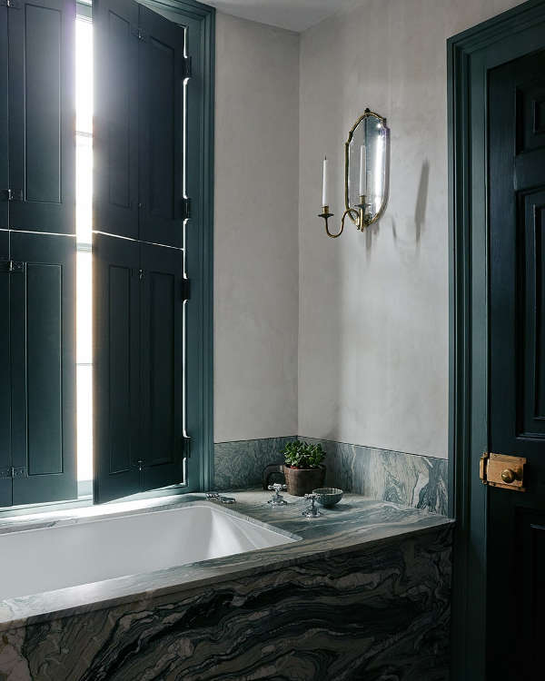 The bathroom features dark green shutters and a door and elegant marble surfaces
