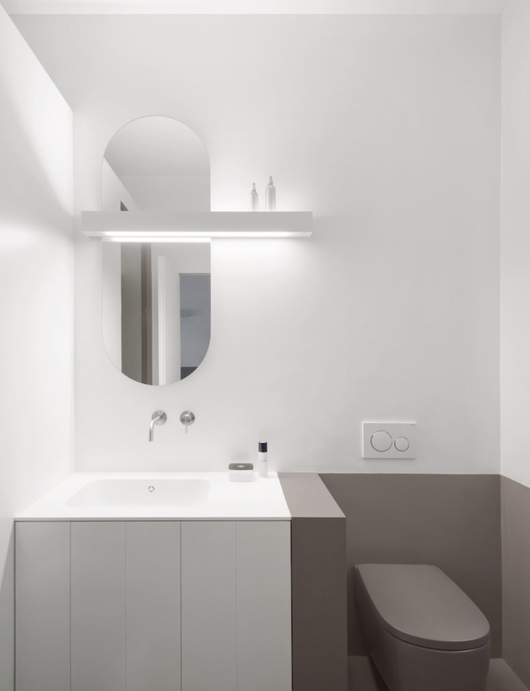 The bathroom is done in grey and white, with minimalist and geometric details