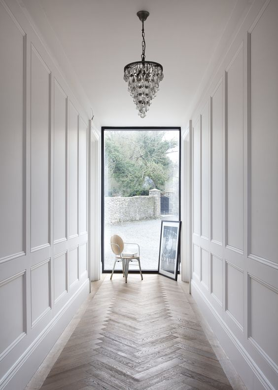 a entrance corridor with paneling and a glam chandelier will impress everyone
