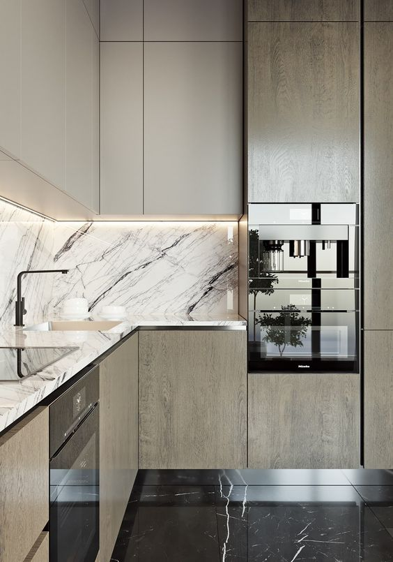 a light-colored wooden kitchen with a chic marble backsplash and countertops for a bold touch