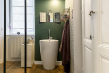 11 The bathroom is done with green and geometric wallpaper, wooden floors and a cool free-standing sink