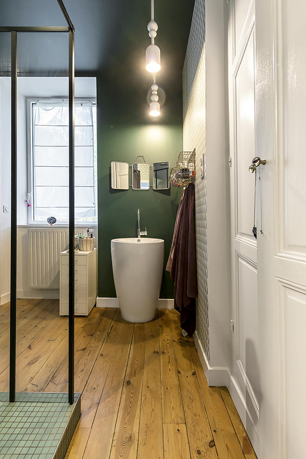 The bathroom is done with green and geometric wallpaper, wooden floors and a cool free-standing sink