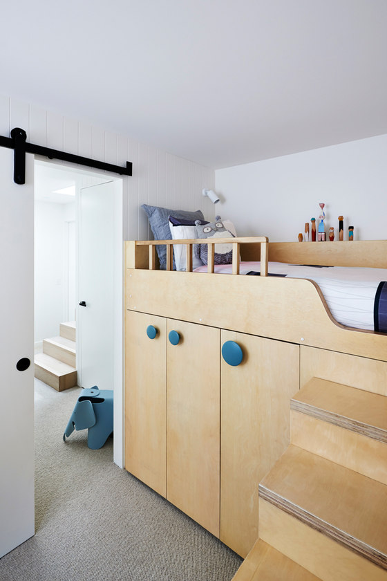 The kid's room has a bunk bed with a wardrobe under it