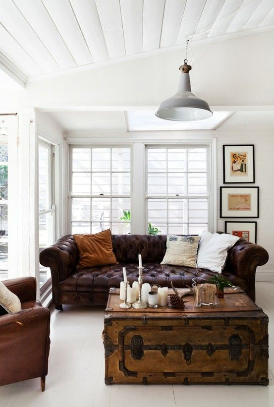 a creamy sunroom with dark leather furniture and a vintage chest for storage