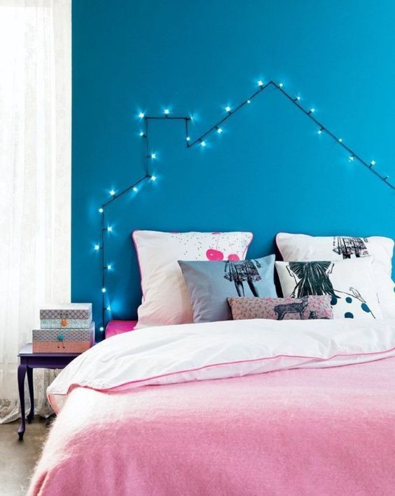 a cute house-shaped headboard made of string lights