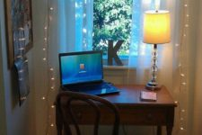 11 a tiny workspace by the window with string lights to enlighten it better