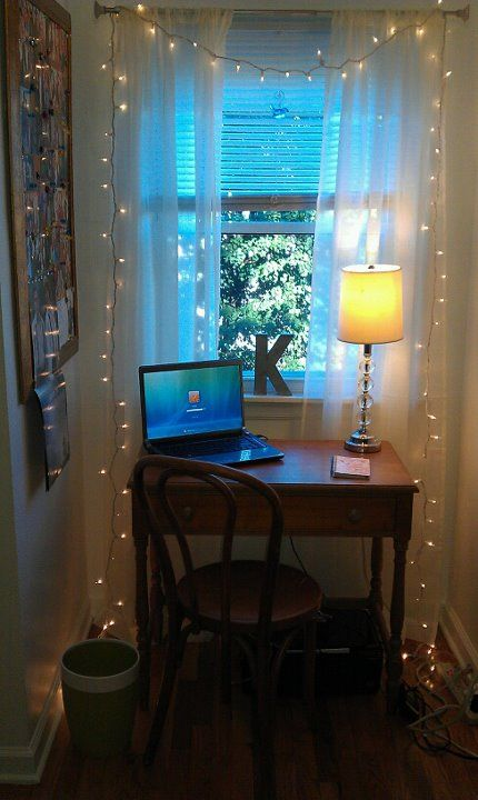 a tiny workspace by the window with string lights to enlighten it better