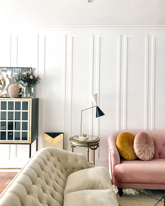molding on the walls adds instant chic to the living room and some pastel touches make it look softer