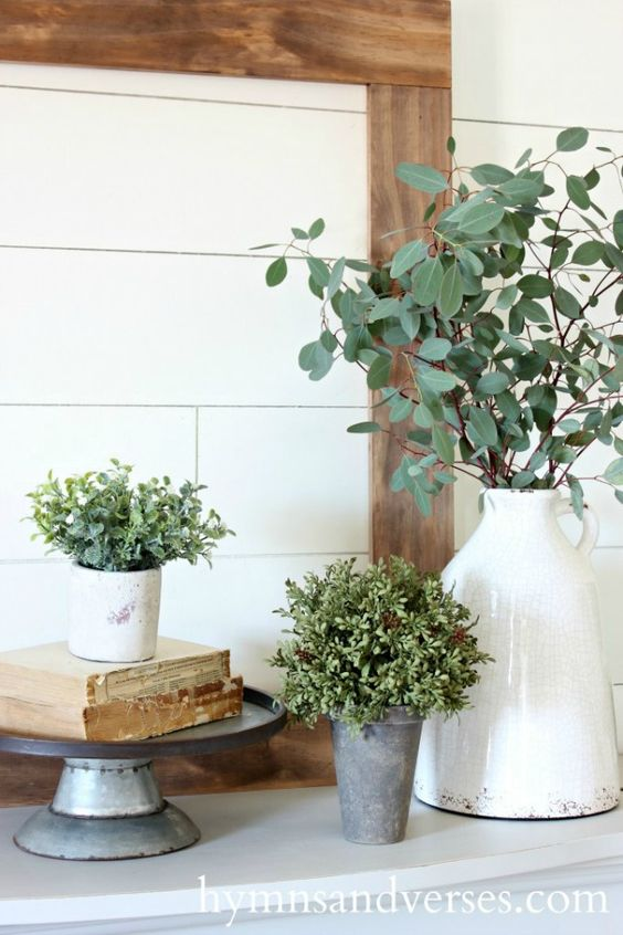 potted greenery and some green branches in a vase for a rustic or farmhouse mantel