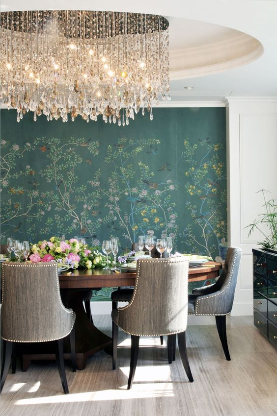 the dining space is accented with a large crystal chandelier hanging from a hole in the ceiling