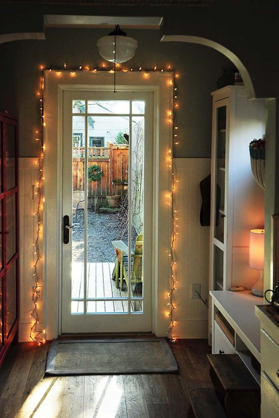 the entry door covered with string lights to add light to the space and highlight the door