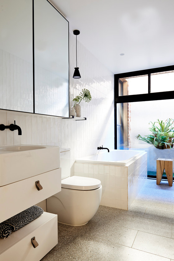 The bathroom is clad with creamy glossy tiles and accented with blacck details