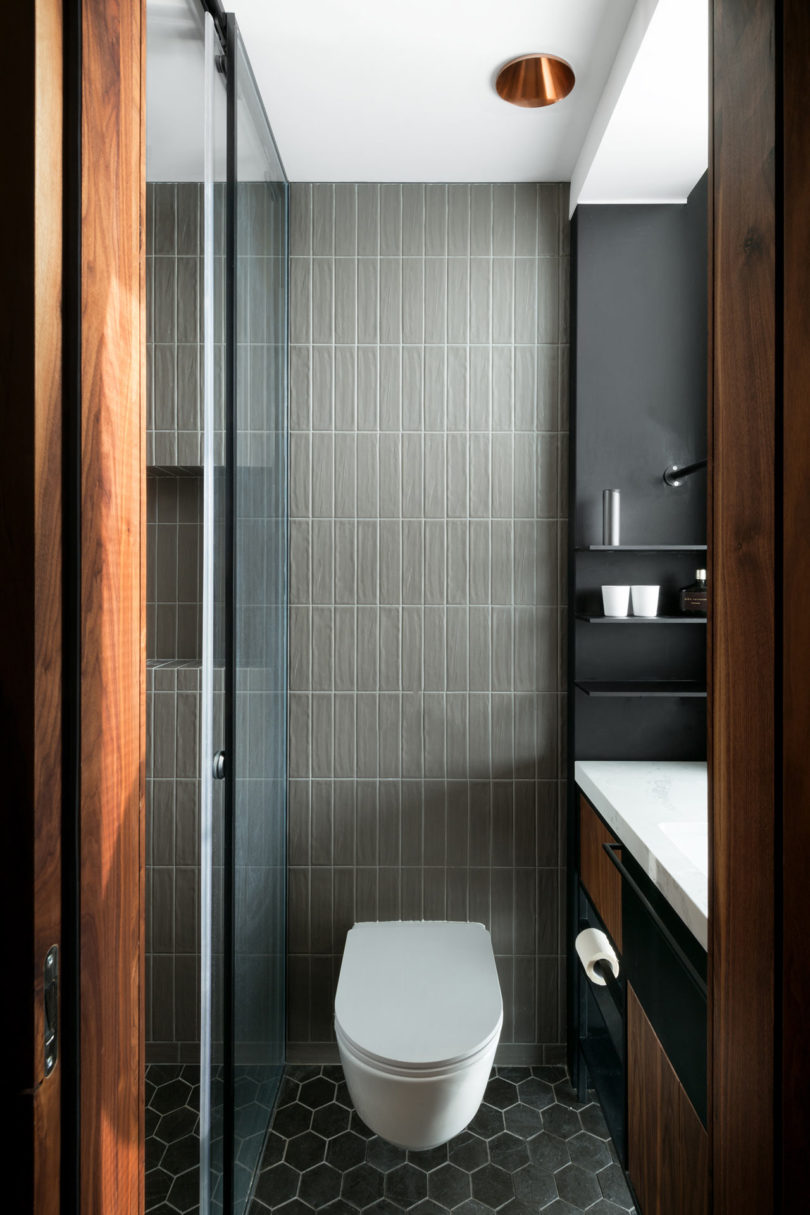 The bathroom is done with the shades of grey and warm colored wood