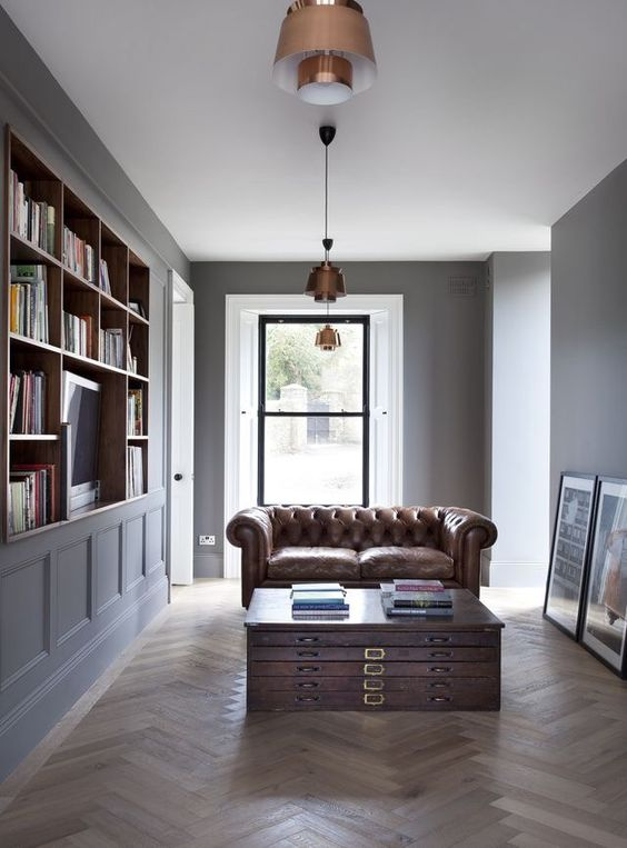 a laconic home library with a unique coffee table and a brown leather sofa