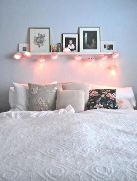 a ledge over the bed with photos and some string lights attached to it