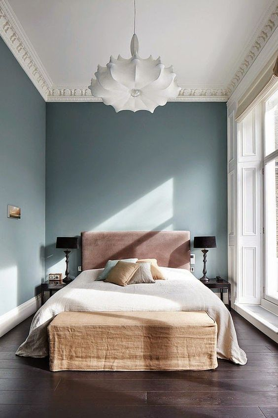 a quirky and whimsy bedroom with interesting furniture, molding and lamps balanced with negative space