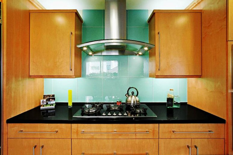 oversized turquoise tiles on the backsplash stand out in a warm-colored kitchen