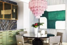 12 the dining space is highlighted with an oversized pink chandelier that contrasts the space