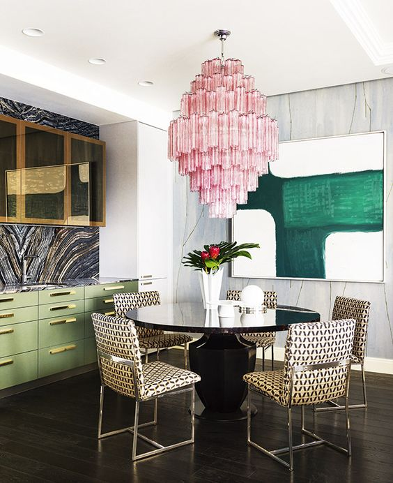 the dining space is highlighted with an oversized pink chandelier that contrasts the space
