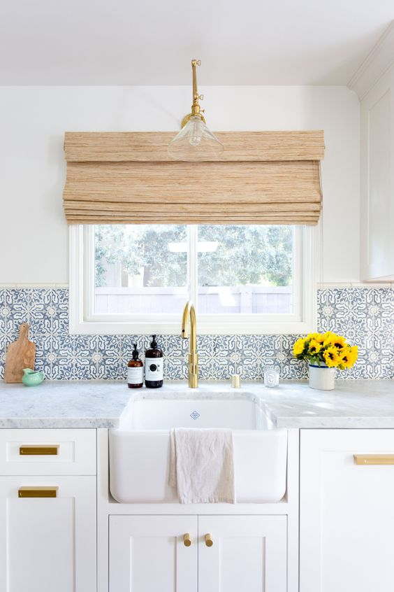 a neutral kitchen is spruced up with blue patterned tiles and brass touches