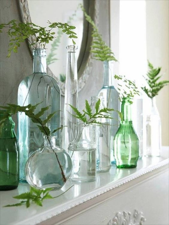 sheer vases and bottles in green shades with leaves in them for a fresh feeling