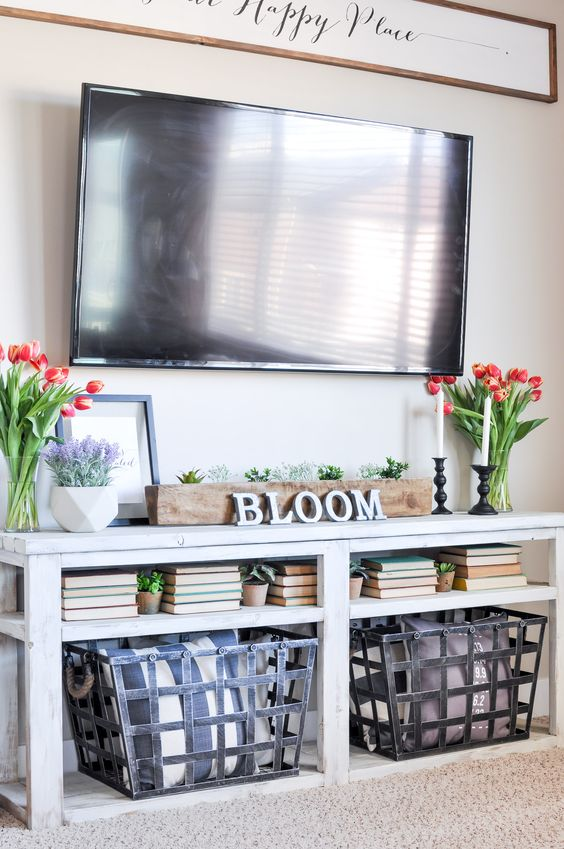 a console table with potted greenery and tulips in vases plus some books