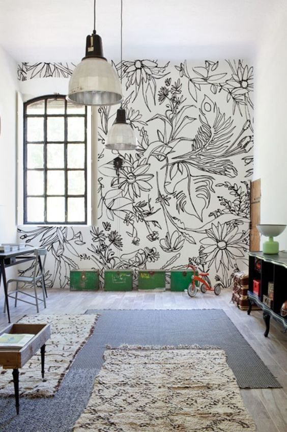 a kid's playroom is accented with a graphic floral wall and matching rugs