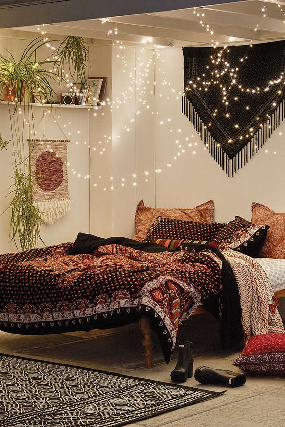 lots of string lights over the bedadd a magical feel to this boho bedroom
