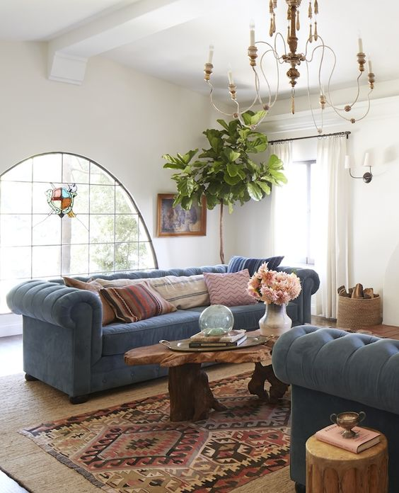 a boho rustic living room with two powder blue Chesterfield sofas that add a calming touch to the bold space