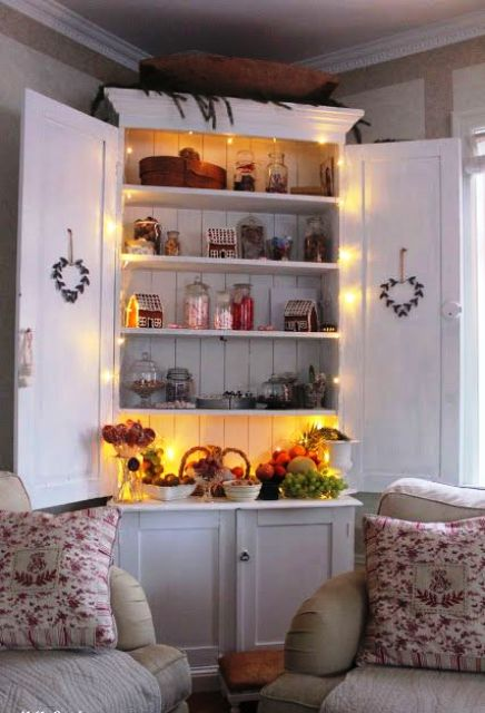 a vintage kitchen cabinet highlighted with string lights can be a display or some bar