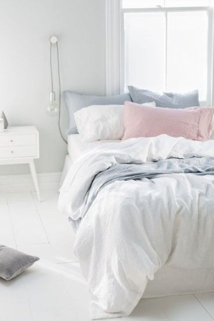 some powder blue and blush pillows will turn a white bed into a springy