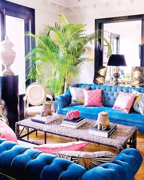 a bold art decor space with bright blue Chesterfield sofas and a woven coffee table