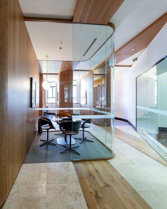 a meeting room inside a home with curved glazed walls