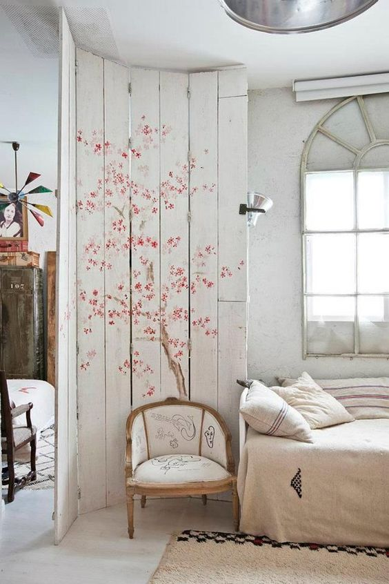 a whitewahsed pallet screen with tender cherry blooms to accent the bedroom