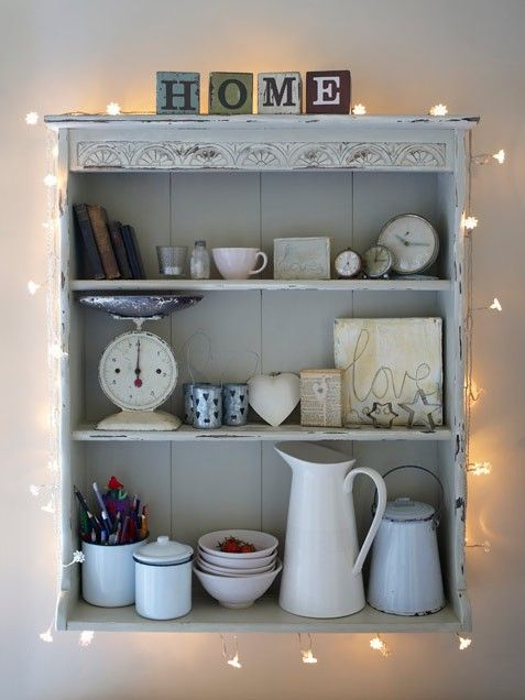 attach some string lights to a usual open cabinet in your kitchen to turn it into a chic display
