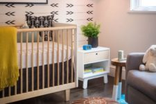 17 a boho nursery with a printed wall, a leather pouf and some rugs plus touches of color