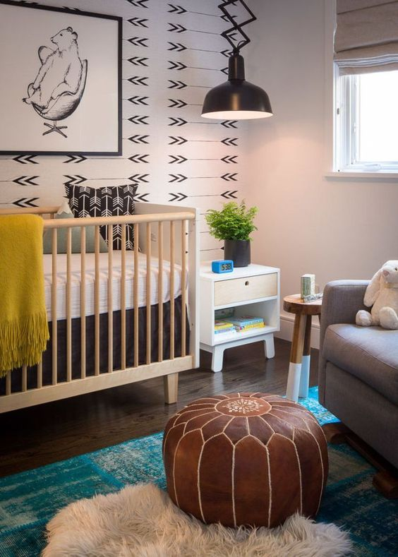 a boho nursery with a printed wall, a leather pouf and some rugs plus touches of color