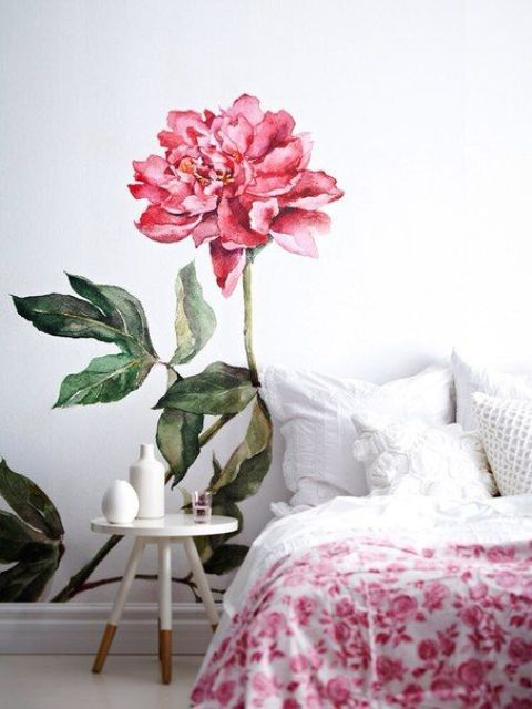 a bold pink bloom painted on the wall next to the bed for a girlish space