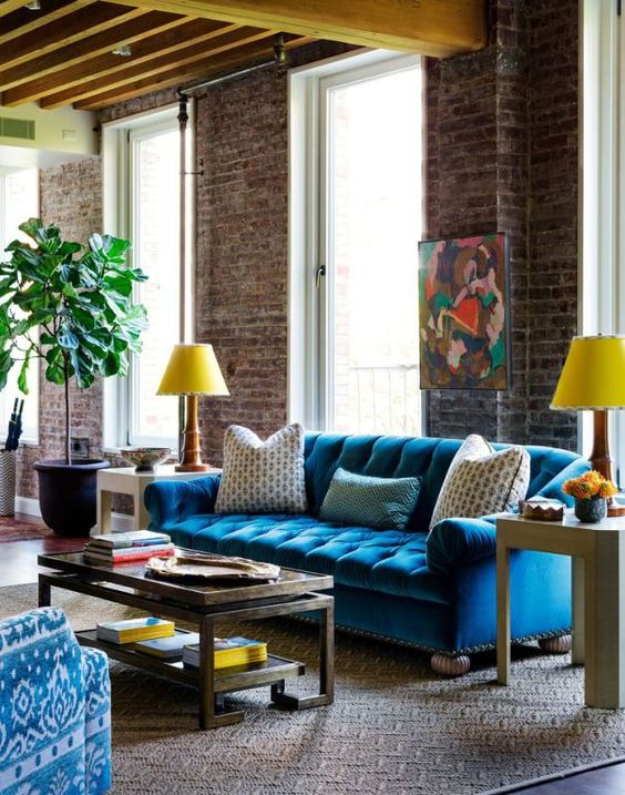 a colorful living room with industrial touches and a bold blue Chesterfield sofa
