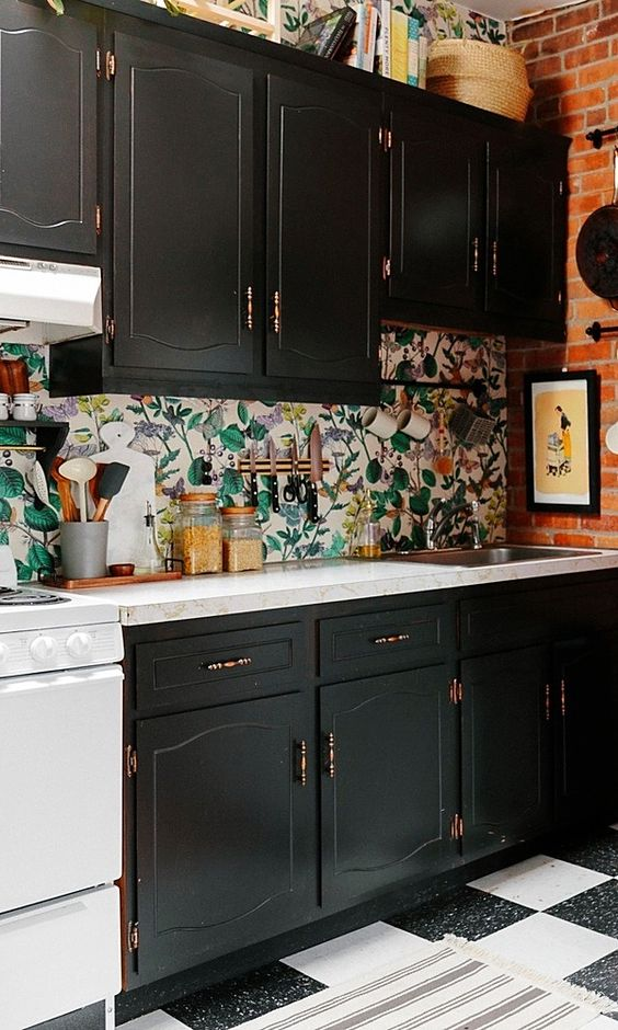 a kitchen backsplash done with floral wallpaper to stand out in a black kitchen